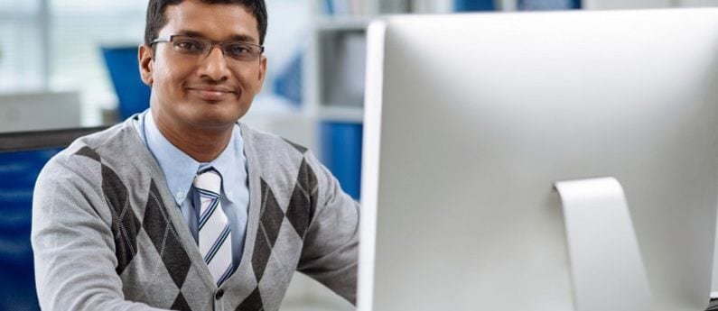 A South-Asian man with glasses, shirt and tie (and a slightly clashing vest) is smiling at you without showing his pearly whites