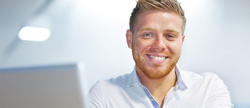 A handsome, reddish-blonde man wearing a smile and a great haircut with a bit too much hair gel is looking right at you