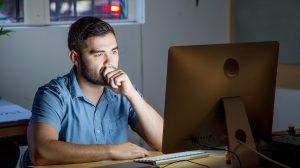 Man looking at computer and frowning