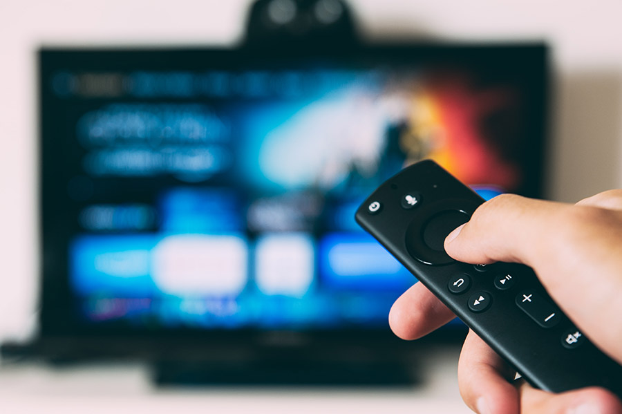 A television remote in front of a blurry screen