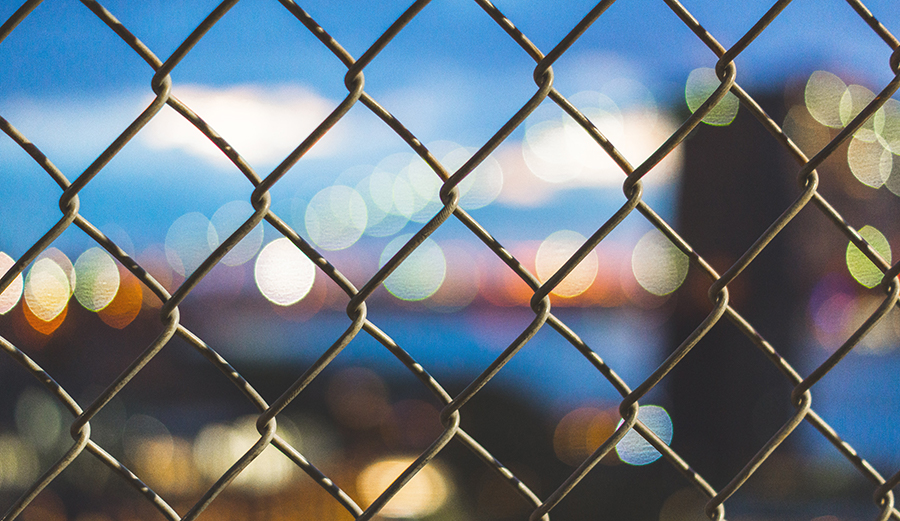 A chain link fence in front of a blurry background