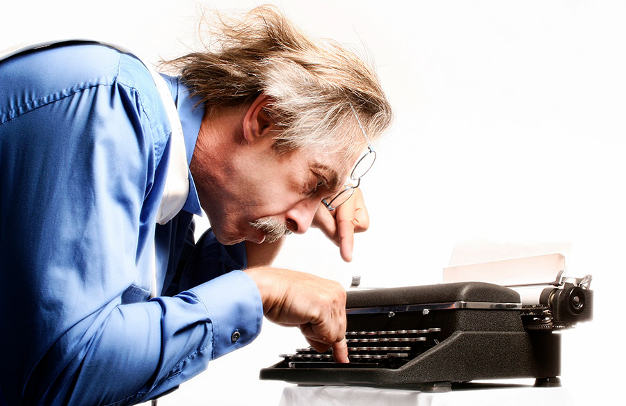 Man using two fingers to type on a typewriter