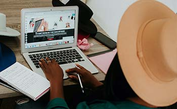 A woman in a hat using a computer
