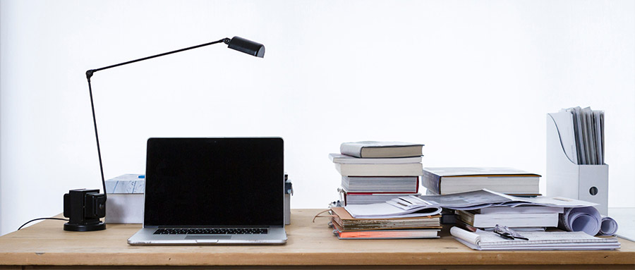 A desk with lamp and laptop