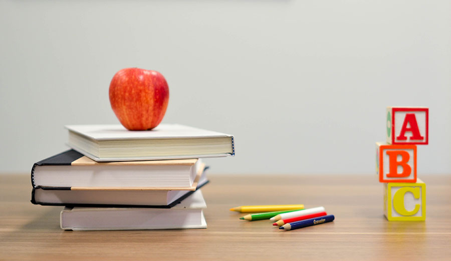 An apple on top of textbooks