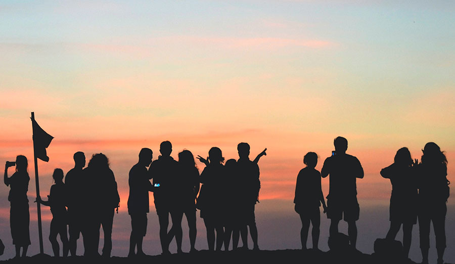 Silhouettes of people standing in front of a sunset