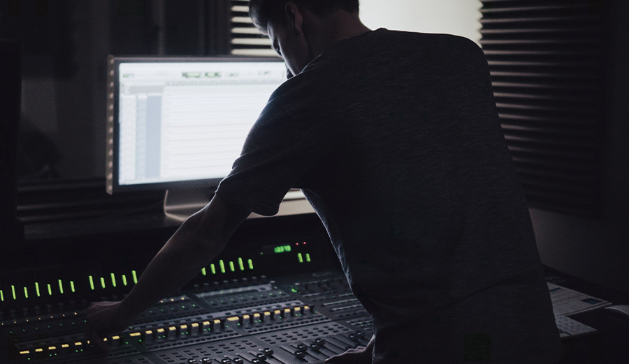 man edits audio on a workstation