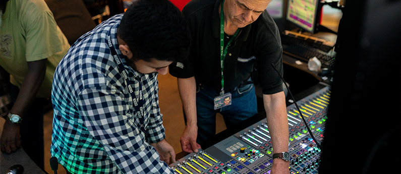 Instructor shows student options on an audio video production workstation