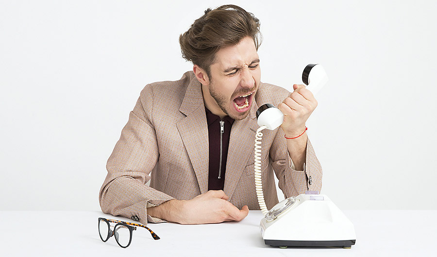Professional looking man yelling into phone