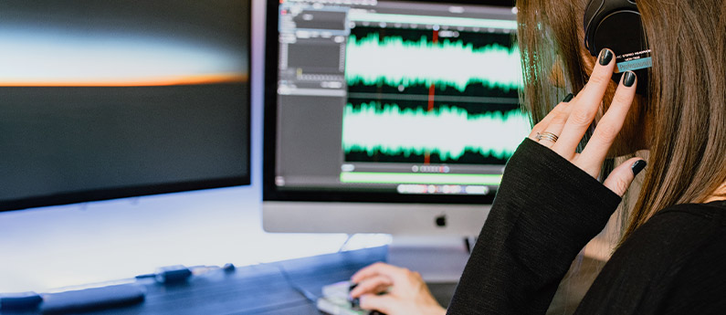 Woman edits audio on a computer