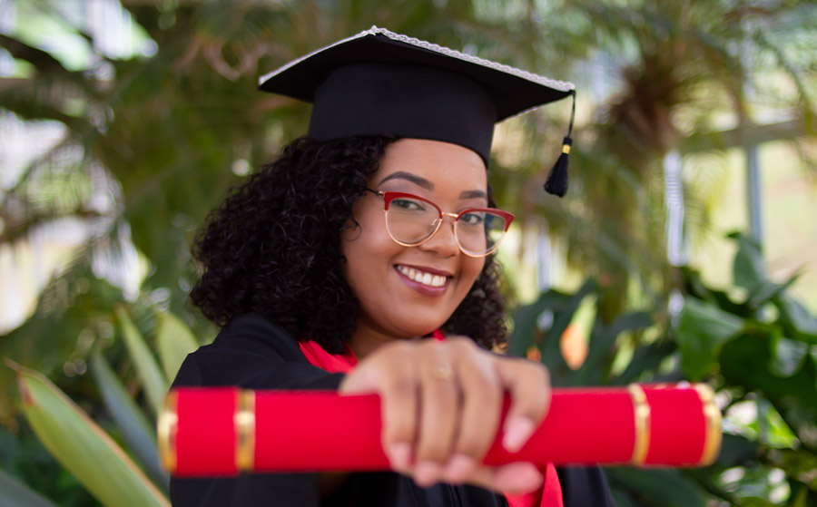 Woman in graduation gown holding diploma