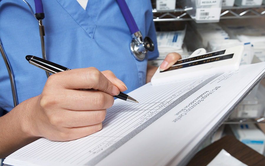 Female doctor writing in patient chart mid section