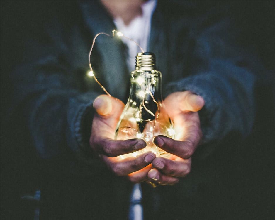 Man holding a lightbulb full of fairy lights